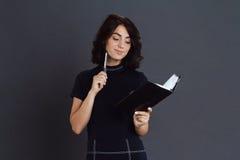 Bella giovane donna premurosa che posa sopra il fondo grigio e che tiene taccuino in mani Immagine Stock Libera da Diritti