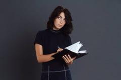 Bella giovane donna premurosa che posa sopra il fondo grigio e che tiene taccuino in mani Fotografia Stock