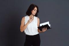 Bella giovane donna premurosa che posa sopra il fondo grigio e che tiene taccuino in mani Fotografia Stock Libera da Diritti