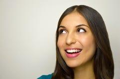 Bella giovane donna sembrando laterale il vostro prodotto su fondo bianco Copi lo spazio Fotografia Stock Libera da Diritti