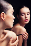 Bella giovane donna sexy vicino allo specchio sopra il nero Fotografia Stock Libera da Diritti