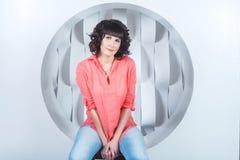 Bella giovane donna sicura che si siede nel cerchio sulla parete di bianco del fondo Fotografia Stock Libera da Diritti