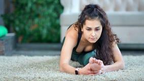 Bella giovane donna sicura di forma fisica della corsa mista che fa allungamento raggiungendo gamba archivi video