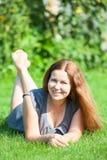 Bella giovane donna sorridente caucasica che riposa sul prato inglese Immagine Stock Libera da Diritti