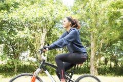 Bella giovane donna sorridente che si esercita con la bicicletta, all'aperto Immagini Stock