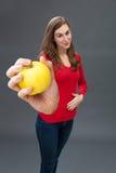 Bella giovane donna sorridente che tocca il suo stomaco per appetito della mela Immagini Stock