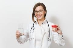 Bella giovane donna sorridente di medico con i vetri dello stetoscopio isolati su fondo bianco Medico femminile in medico immagine stock
