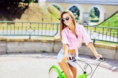 Bella giovane donna sorridente felice su una bicicletta Immagini Stock Libere da Diritti