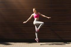 Bella giovane donna sportiva che posa contro la parete marrone Immagine Stock