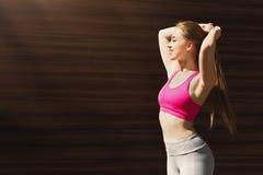 Bella giovane donna sportiva che posa contro la parete marrone Fotografia Stock