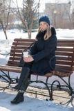 Bella giovane donna su un banco un il giorno di inverno soleggiato con un coffe fotografia stock libera da diritti