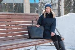 Bella giovane donna su un banco un il giorno di inverno soleggiato con una grande b immagine stock