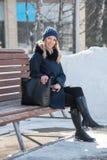 Bella giovane donna su un banco un il giorno di inverno soleggiato con una grande b fotografia stock
