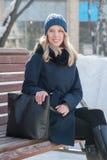 Bella giovane donna su un banco un il giorno di inverno soleggiato con una grande b immagini stock libere da diritti