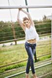 Bella giovane donna su un campo di football americano verde Ragazza che sta al portone di calcio, vestito in blue jeans, una magl Immagine Stock