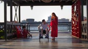 Bella giovane donna su una passeggiata con un giovane in una sedia a rotelle nella sera di estate fotografia stock libera da diritti