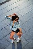 Bella giovane donna sui pattini di rullo e su un casco rosa fotografia stock