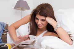 Bella giovane donna sulla rivista della lettura del letto Fotografie Stock