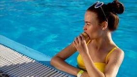Bella giovane donna in swimwear che mangia gelato mentre stando nello stagno video d archivio