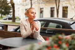 Bella giovane donna in un cappotto alla moda che riposa in un caffè immagini stock libere da diritti