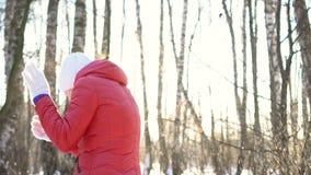 Bella giovane donna in un parco soleggiato di inverno, giocando le palle di neve, divertendosi, sorridente Movimento lento video d archivio