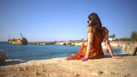 Bella giovane donna in un vestito che si siede dalla riva rocciosa sui precedenti della vista pittoresca di vecchia nave, cielo e video d archivio