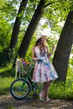 Bella giovane donna in un vestito ed in un cappello su una bicicletta sul nazionale Fotografia Stock