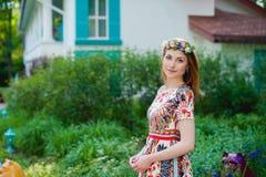 Bella giovane donna in una corona dei fiori ed in un vestito luminoso che si siede sul ritratto in natura, la gioia dell'erba di  Fotografia Stock Libera da Diritti