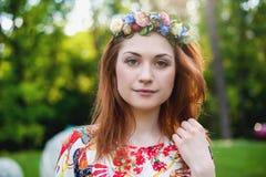 Bella giovane donna in una corona del ritratto sorridente dei fiori sulla natura, la gioia di vita, sorriso Fotografia Stock Libera da Diritti
