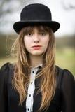 Bella giovane donna vestita in cappello di giocatore di bocce d'uso nero Fotografia Stock Libera da Diritti