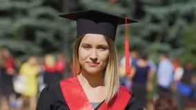 Bella giovane donna in vestito accademico che guarda alla macchina fotografica, riuscito laureato video d archivio