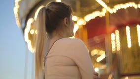 Bella giovane donna in vestito che sta al carosello illuminato giusto e di sguardo video d archivio