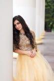Bella giovane donna in vestito dall'oro Fotografia Stock