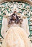 Bella giovane donna in vestito dall'oro Fotografia Stock Libera da Diritti