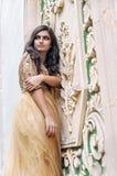 Bella giovane donna in vestito dall'oro Immagini Stock Libere da Diritti