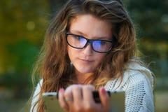 Bella giovane donna in vetri con la compressa nel parco di autunno fotografia stock