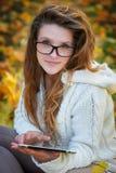 Bella giovane donna in vetri con la compressa nel parco di autunno fotografia stock libera da diritti