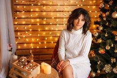 Bella giovane donna vicino all'albero di Natale in un maglione bianco, in un nuovo anno aspettante accogliente e nelle feste di N fotografie stock libere da diritti