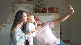 Bella giovane famiglia che prende un selfie in cucina archivi video