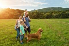 Bella giovane famiglia con il loro cane di animale domestico fotografia stock