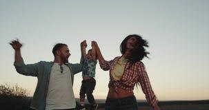 Bella giovane famiglia sorridente, tre membri, papà della mamma e la loro camminata felice del figlio del bambino attraverso il c video d archivio