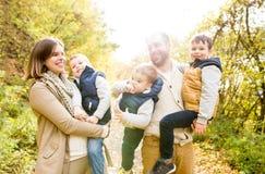 Bella giovane famiglia su una passeggiata nella foresta di autunno Immagini Stock