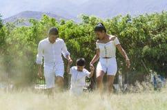Bella giovane famiglia su una passeggiata nella foresta di estate fotografie stock libere da diritti