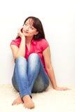 Bella giovane femmina che si siede dalla parete Immagine Stock Libera da Diritti