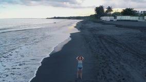 Bella giovane femmina sulla spiaggia dell'oceano con la sabbia nera e delle onde al tramonto su Bali, video 4K degli aerei stock footage