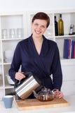 Bella giovane donna felice che prepara tè a casa fotografia stock libera da diritti