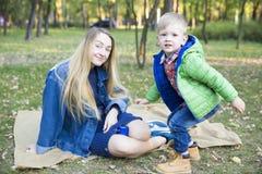 Bella giovane madre con capelli lunghi con il piccolo figlio che gioca si Fotografia Stock