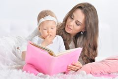 Bella giovane madre con il libro di lettura della figlia Fotografia Stock