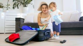 Bella giovane madre con la valigia dell'imballaggio del ragazzo del bambino per la vacanza immagini stock libere da diritti