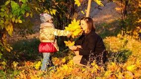 Bella giovane madre con una piccola figlia divertendosi nel parco di autunno video d archivio